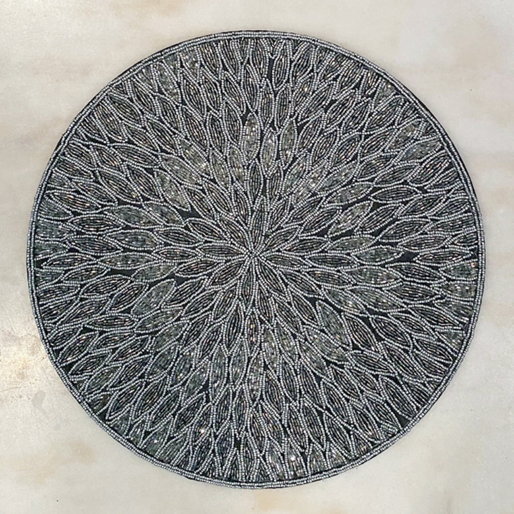 A gray table cloth with a place setting.  Placemat has scalloped edges and a large colorful floral pattern.  A white plate with boxwood candle ring is on top, and on top of those is a coordinating napkin to the placemat bound in a shiny metal napkin ring.