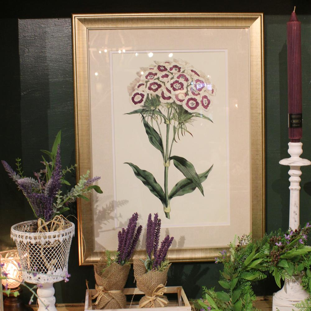 Framed floral art on a green wall with a variety of lavender and spring greens in front.
