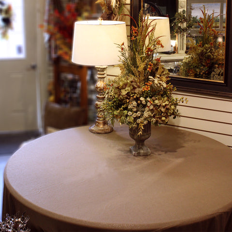 empty table with tan tablecloth, a small lamp and a fall floral arrangement