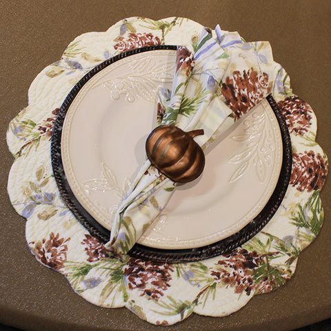 a fan folded napkin in a copper pumpkin napkin ring, on top of a white ceramic plate, on top of a dark brown charger plate, on top of a floral placemat, on top of a tan tablecloth