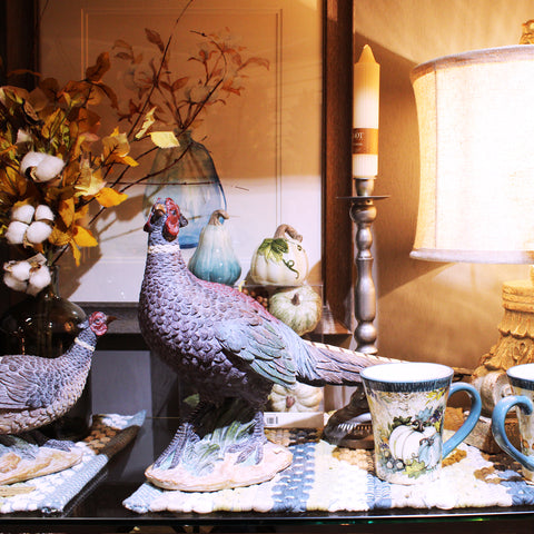 pheasants on a shelf with striped placemats, a framed photo of flowers, an arrangement of cotton, and a lit lamp