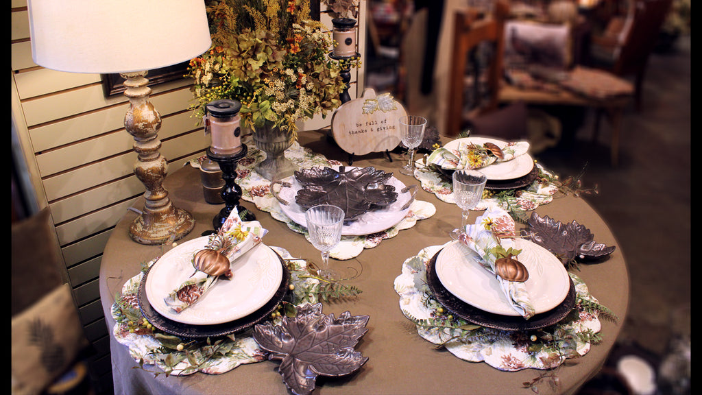 set dinner table, with three place settings and a floral center piece.  white dishes and serving tray with dark gray maple leaf shaped salad dishes.  each place setting has a folded napkin inside of a copper pumpkin napkin ring, on top of a white ceramic plate, dark brown charger plate, floral ring coordinating with the centerpiece and placemat.