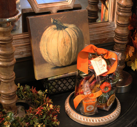 a small canvas with a white pumpkin print behind a bag of potpourri with an orange bow