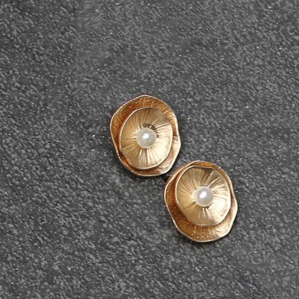 A pair of gold earrings, each feature a pair of layered gold concave pieces with a pearl detail in the middle.