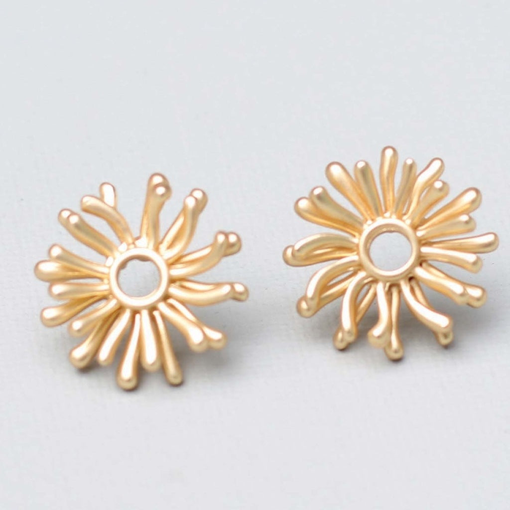 A pair of gold stud earrings.  The center is an open circle and radiating from it are rays of gold reminiscent of an abstract sun.