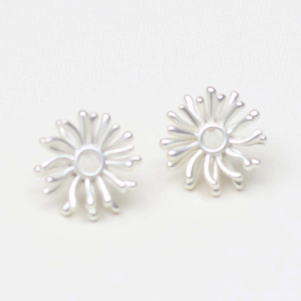 A pair of silver stud earrings.  The center is an open circle and radiating from it are rays of silver reminiscent of an abstract sun.