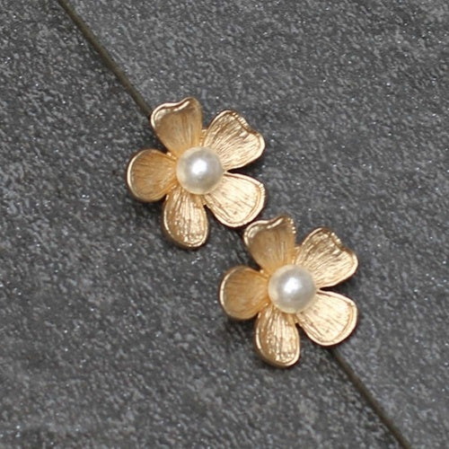 A pair of five petal floral stud earrings, each with a pearl detail in the middle.