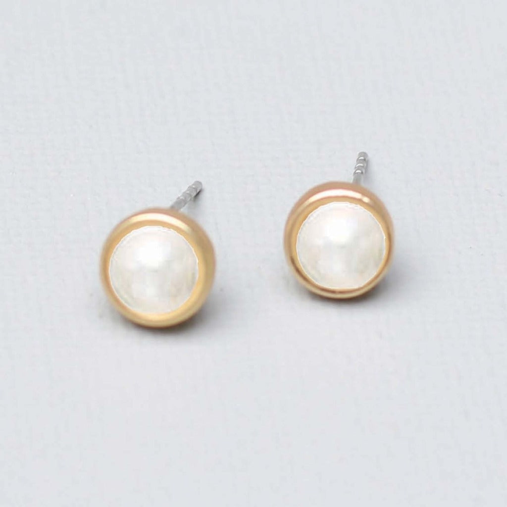 A pair of stud earrings.  A pearl center surrounded by a thin band of gold.