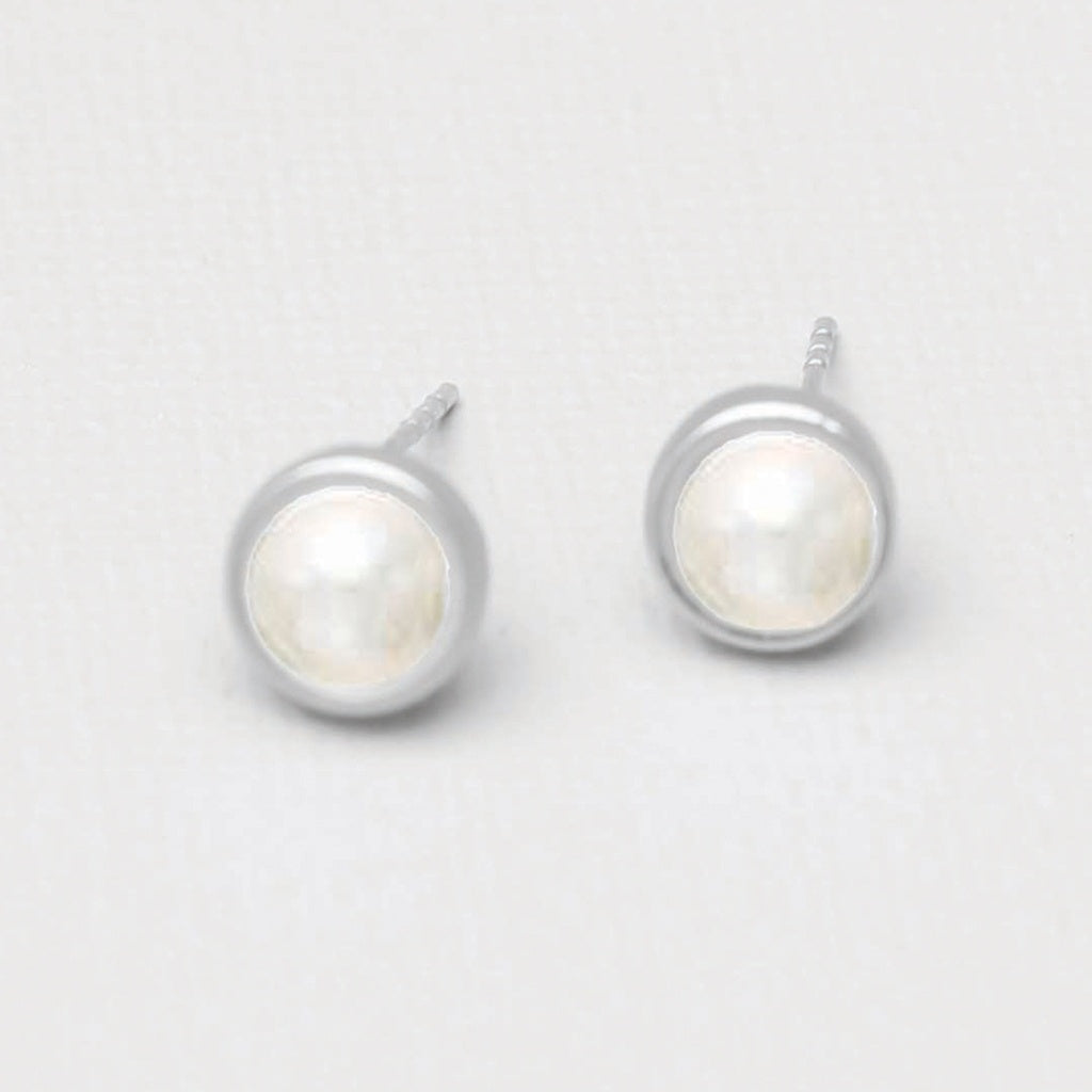 A pair of stud earrings.  A pearl center surrounded by a thin band of silver.