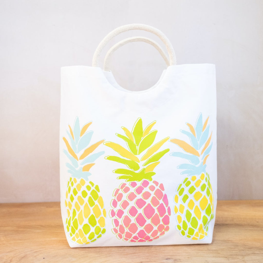 An image of a white tote with arced jute handles on a wooden surface in front of a white wall.  The bag has three pineapples printed on the side in neon colors.  The middle pineapple has leaves of lime green and bright yellow, and the body of it is hot pink and neon orange.  On either side of that pineapple are ones with blue and orange leaves, and yellow and green bodies.