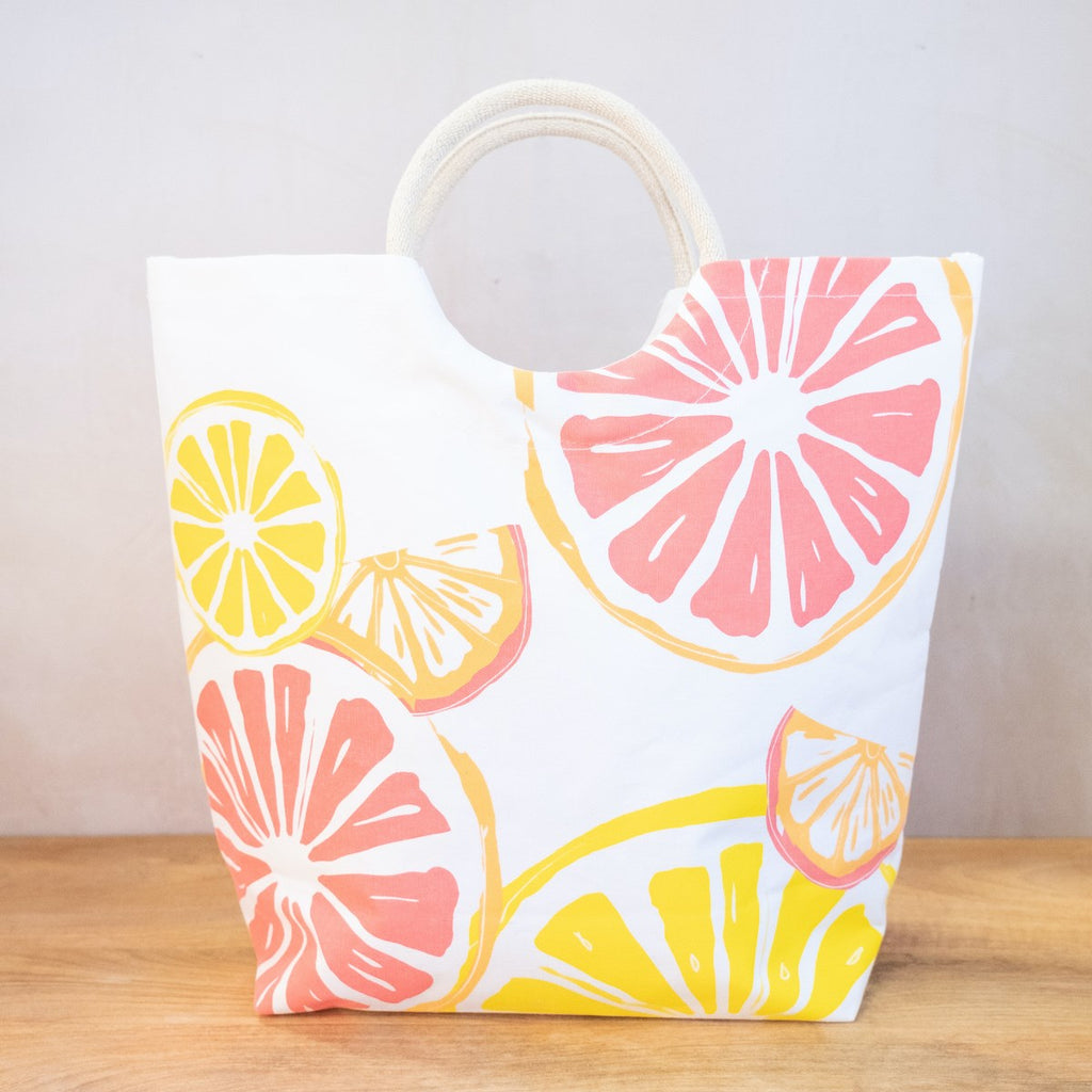 A white tote on a wooden surface in front of a white wall.  The tote has arched handles and a variety of fruit slices printed on the side in yellows, oranges and pinks.