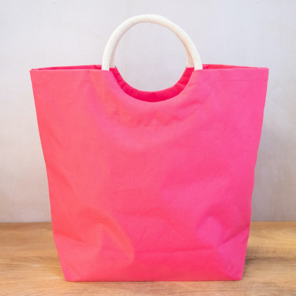 A hot pink tote bag on a wooden surface in front of a white wall.  The bag has arched jute handles and the bag has a semi circle cut below the handle, making a circle of negative space under the handle.
