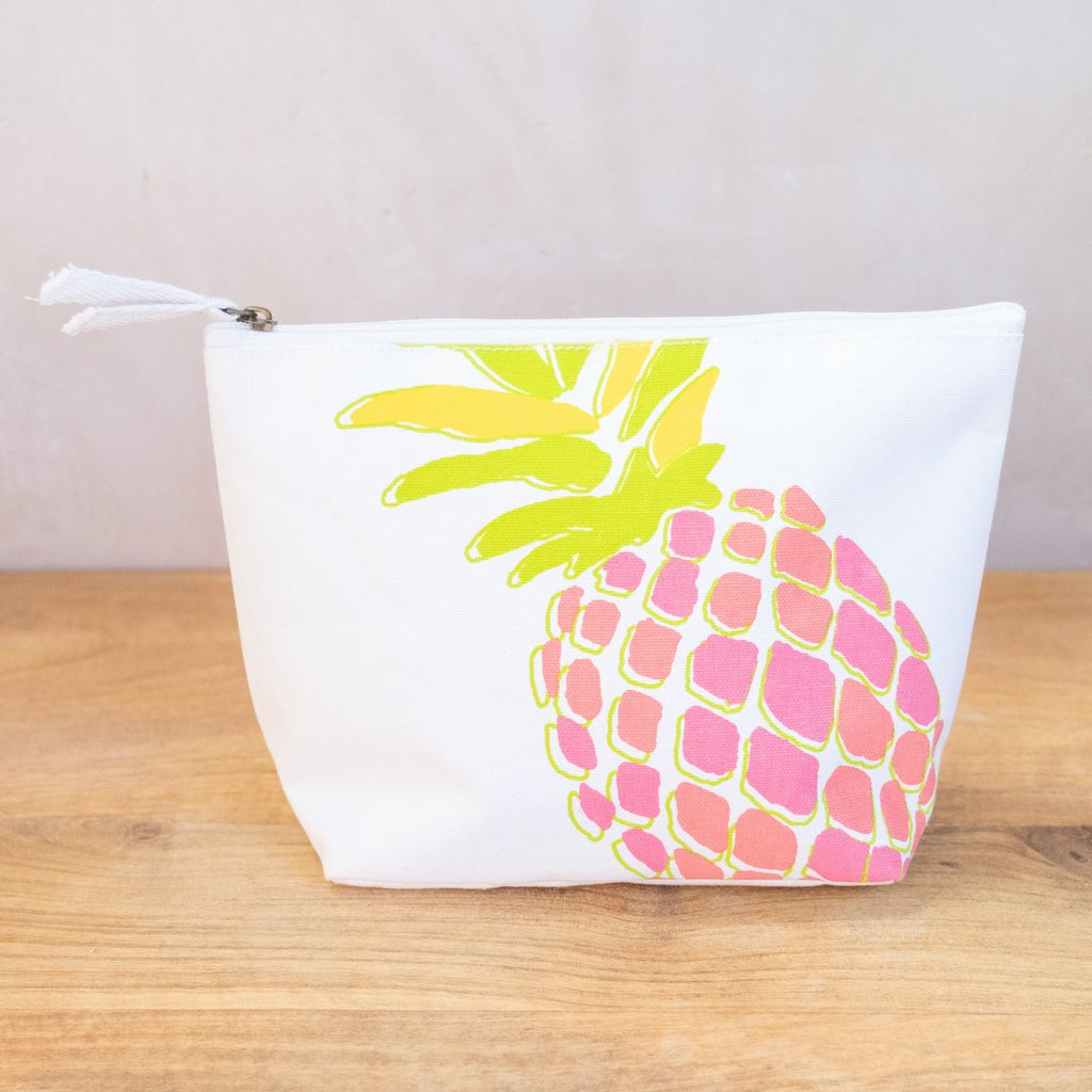 An image of a white cosmetic bag on a wooden surface in front of a white wall.  The cosmetic bag has a zipper on top with two white fabric pulls.  The side of the bag has a neon pineapple printed on it at an angle (so the top and bottom are cut off).  The pineapple has green and yellow leaves and has pink and orange coloration on the body.