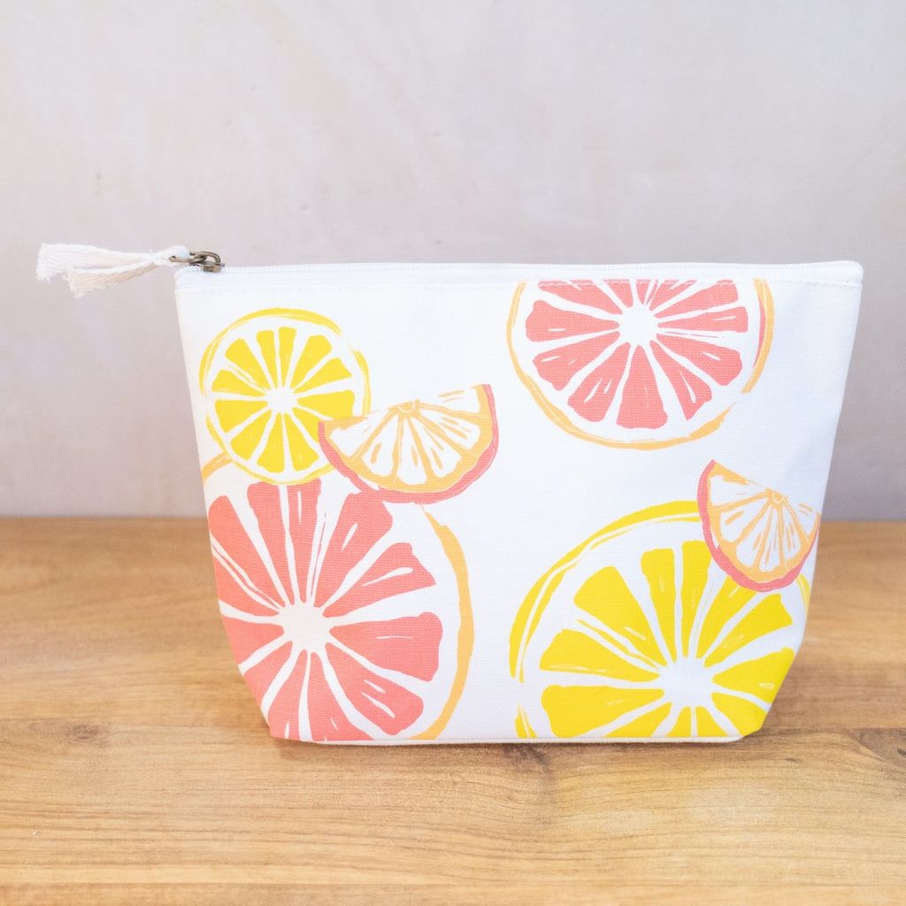 A white cosmetic bag on a wooden surface in front of a white wall.  On the side of the bag are a variety of fruit slices printed on it in orange, yellow, and pink.  The bag has a zipper at the top with two fabric ties.