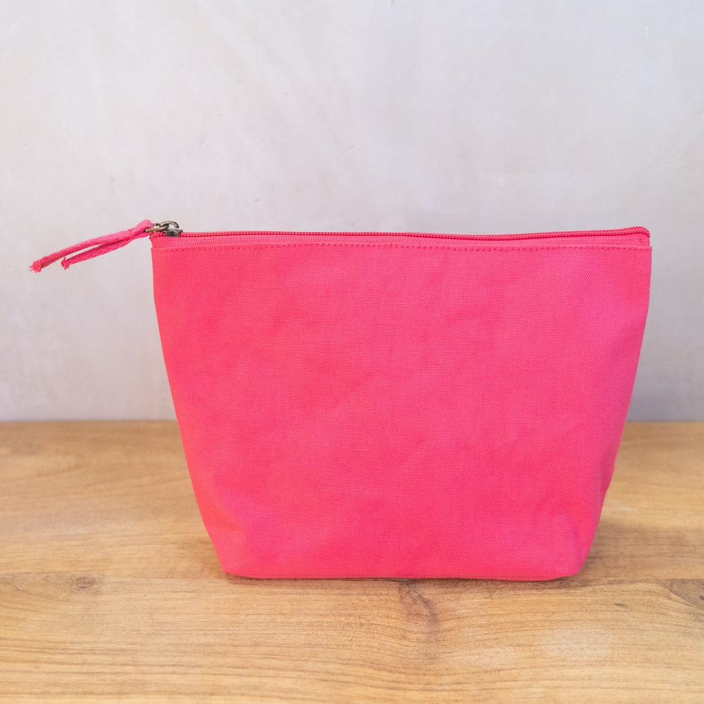 A hot pink cosmetic bag on a wooden surface in front of a white wall.  The bag has a zipper across the top and two pieces of fabric as a pull on the zipper.