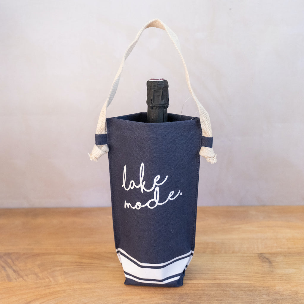 A navy blue canvas bag with white stripe at the bottom.  The handle is a wide jute strap.  Inside the bag is a bottle of champagne.