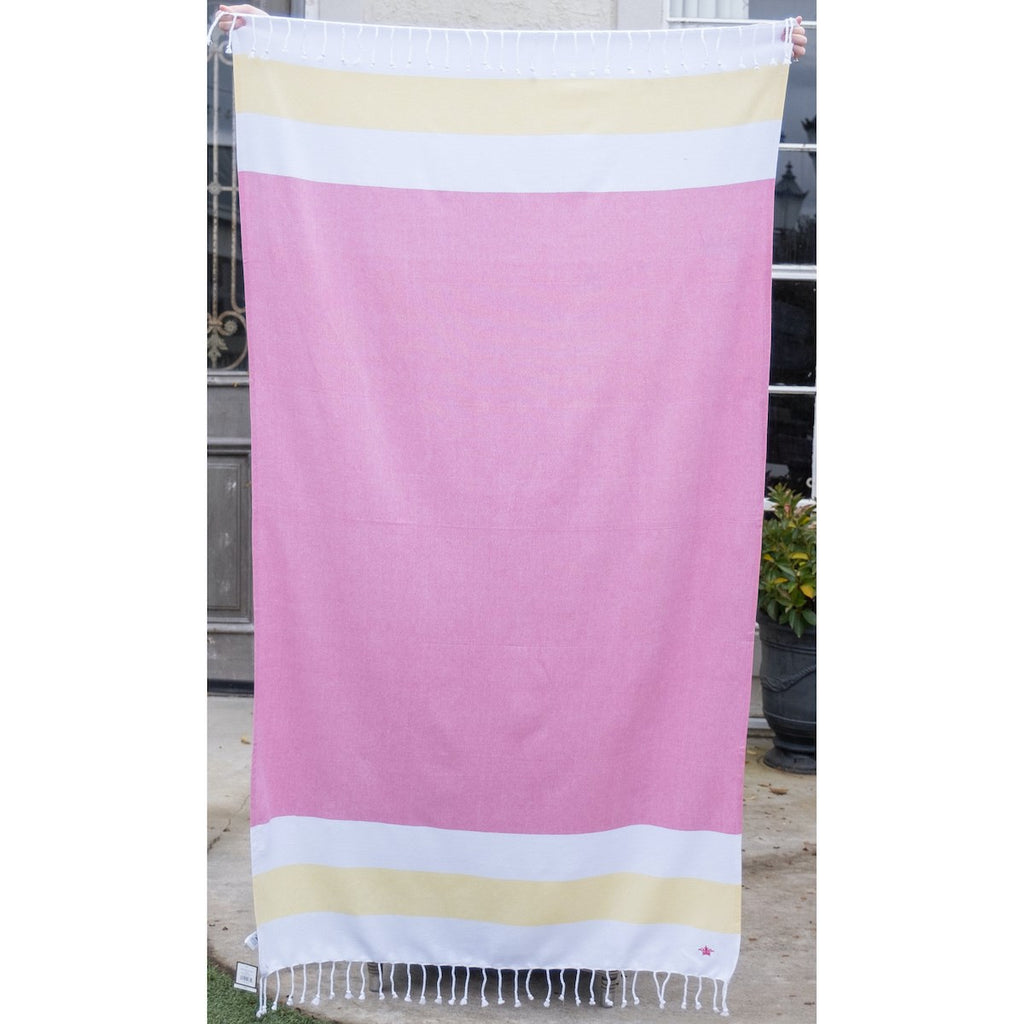 A pink beach towel with stripes at the top and bottom.  The stripes are wide and horizontal, white, yellow, white.  There is white fringe along the top and bottom of the towel.