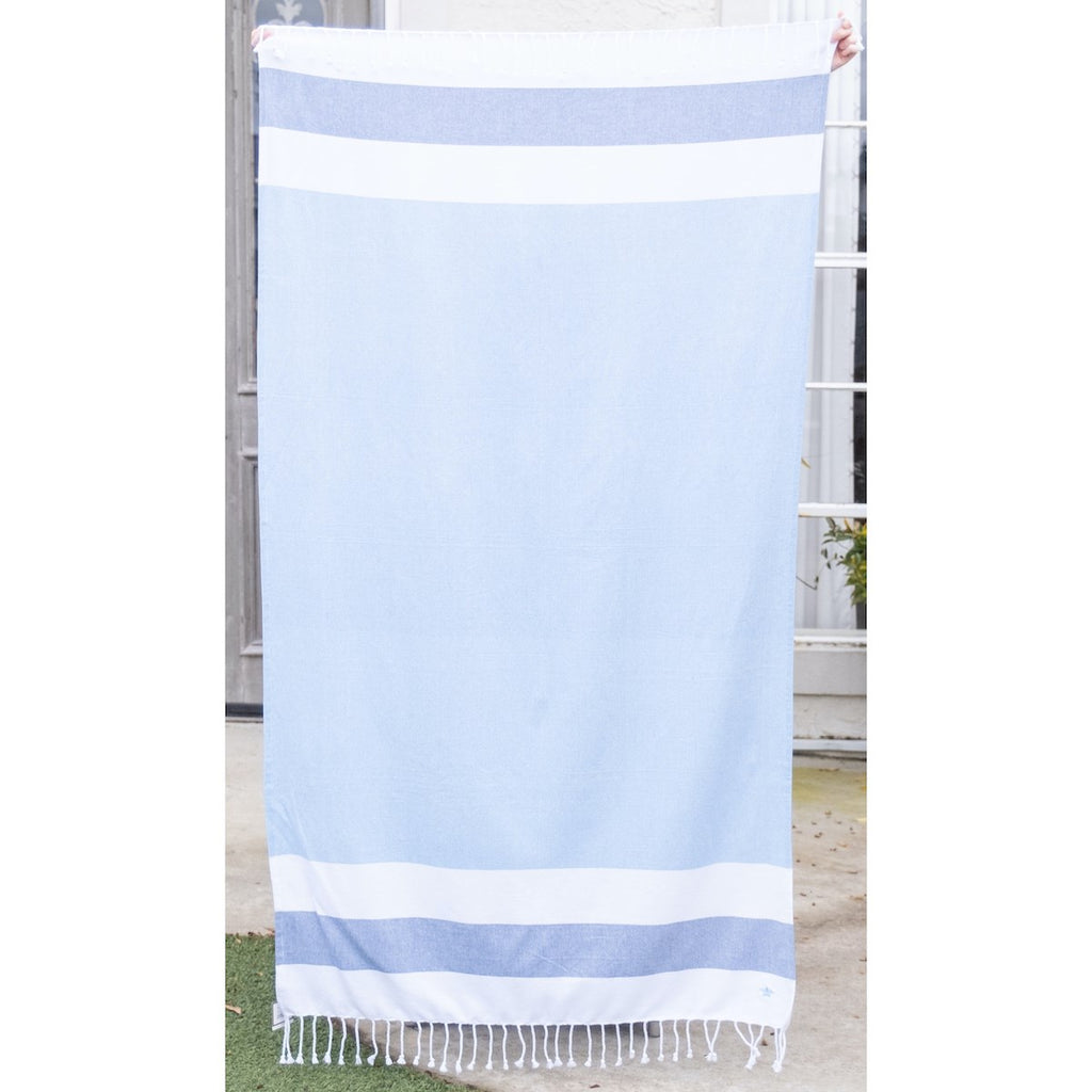 A light blue beach towel with stripes at the top and bottom.  The stripes are wide and horizontal, white, dark blue, white.  There is white fringe along the top and bottom of the towel.