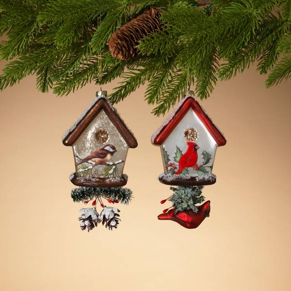 Two glass birdhouse ornaments handing from an evergreen garland.  Ornament on the left is a brown roofed birdhouse with a small brown bird painted below the birdhouse opening.  Below the birdhouse is a small piece of evergreen and two flocked pinecones.  The birdhouse on the right has a red roof, and an image of a cardinal in front of holly below the opening.  The bottom of the birdhouse has a piece of flocked holly and a glass dimensional cardinal hanging from it.