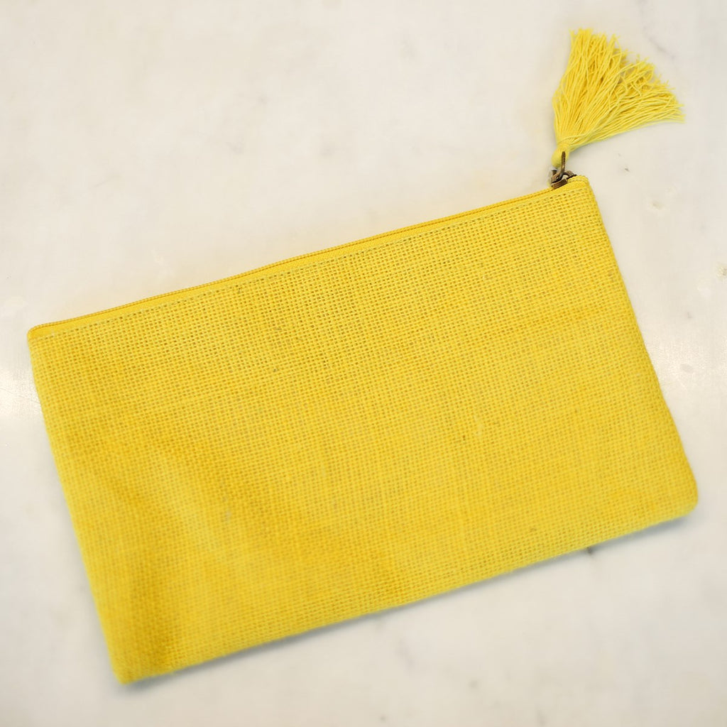 A lemon yellow jute cosmetic bag with a yellow tassel attached to the zipper.