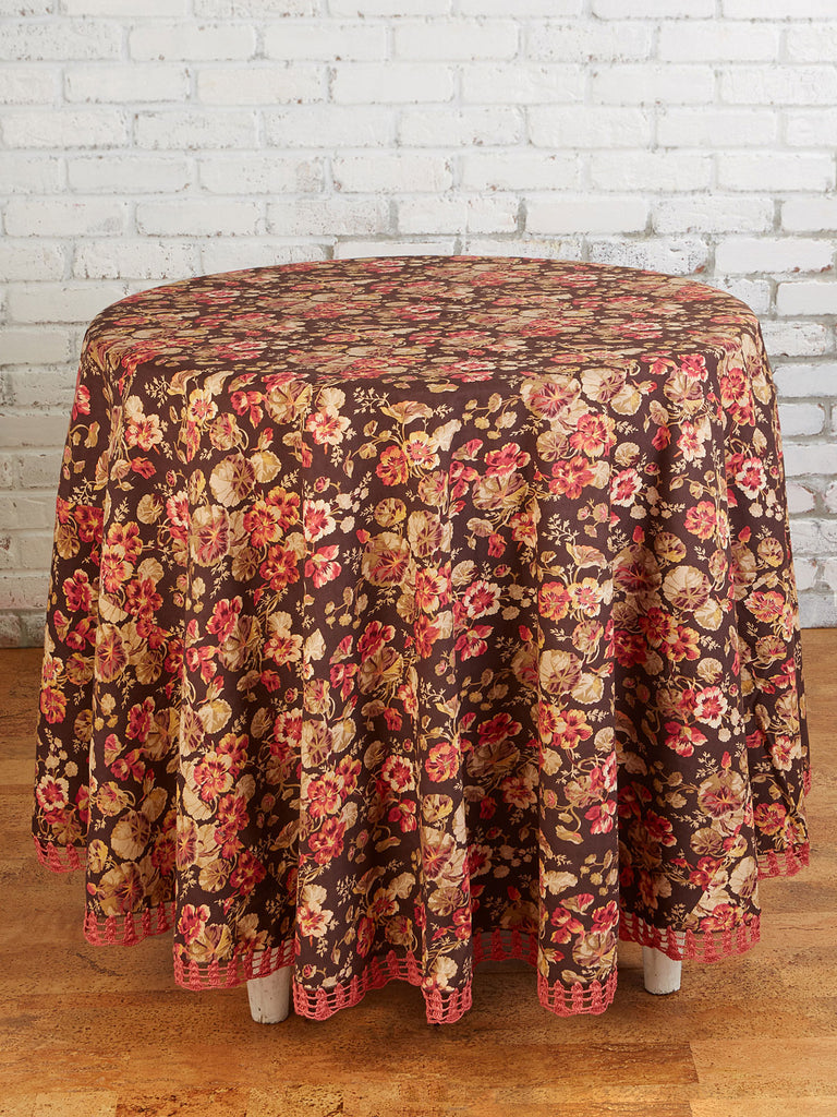 Floral tablecloth on a round table in front of a white brick wall.  Table cloth has a dark brown background, tan and red flowers, and a woven dark pink bottom detail.