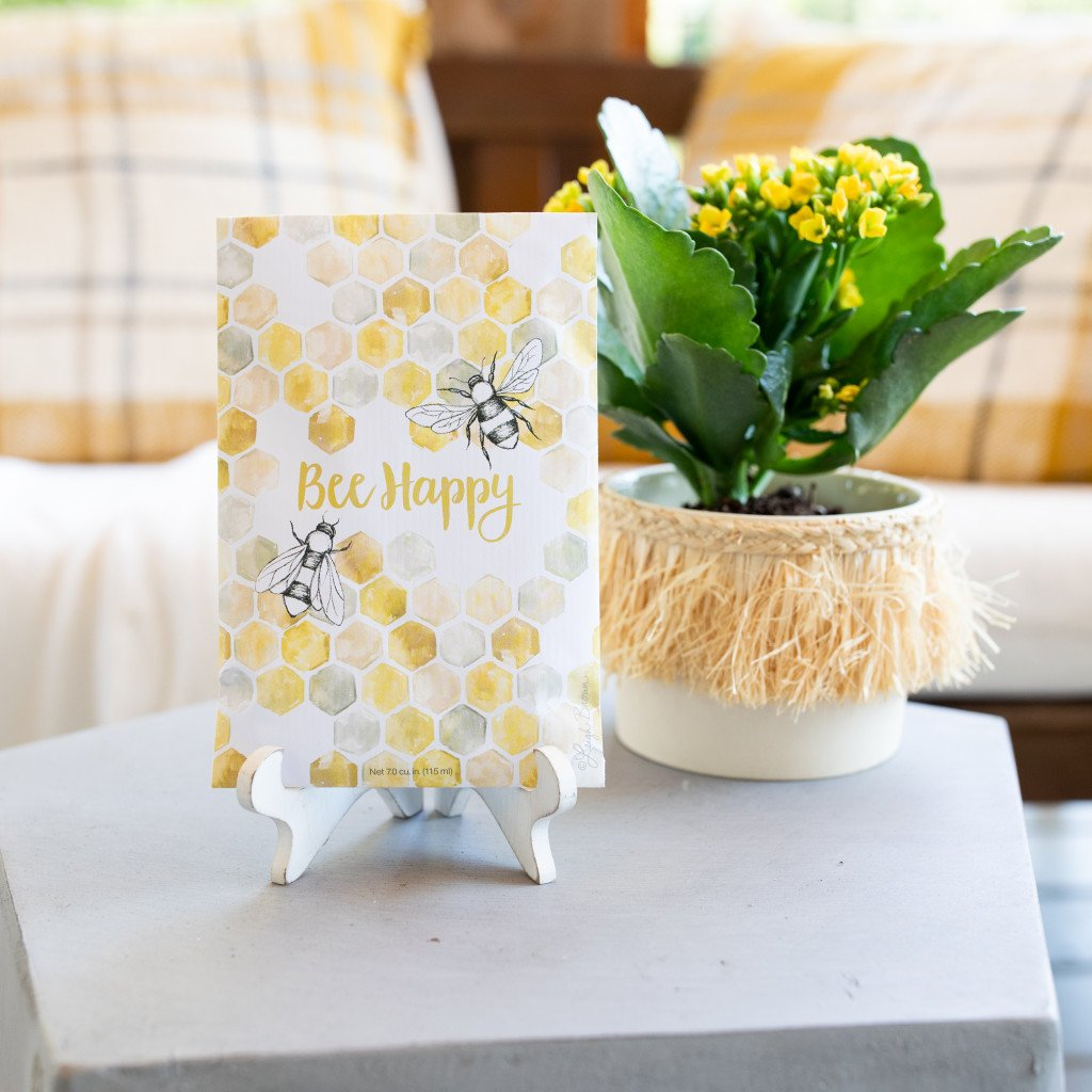 A sachet on an easel on top of a gray table.  Behind the sachet is a flower in a pot with tassel trim.  The sachet has an image of hexagons linked together like a hive with two bees on it, and the text 'Bee Happy'