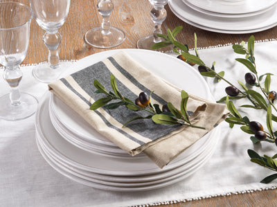 A place setting on a wooden table with a stack of white plates on a white runner.  On top of the plates is a folded tan napkin with a thick gray stripe and a thin gray stripe on either side of it.  On top of the napkin is a decorative olive branch.