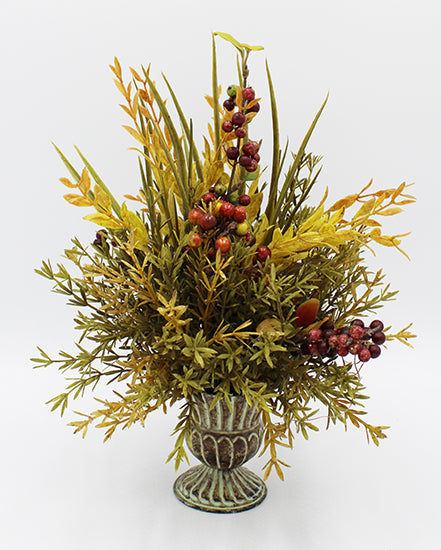 Floral arrangement with red berries in a green urn.