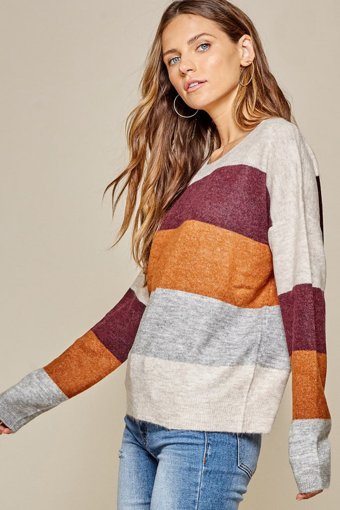 Model wearing a color block horizontal striped sweater.  Gray around neck, then a thick stripe of burgundy, orange, repeated gray, and the bottom is off white.