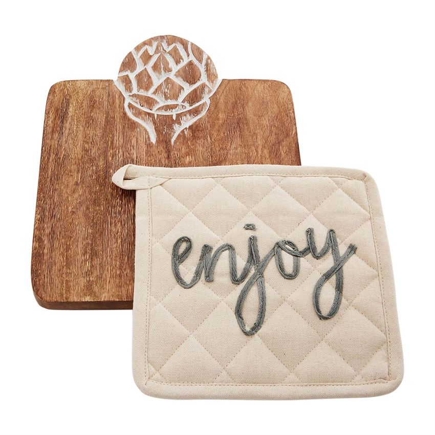 A square wooden trivet with engraved artichoke detail at the top.  The engraving is white.  On top of the trivet is a quilted off white potholder with embroidery that says 'enjoy' in cursive lowercase gray font.