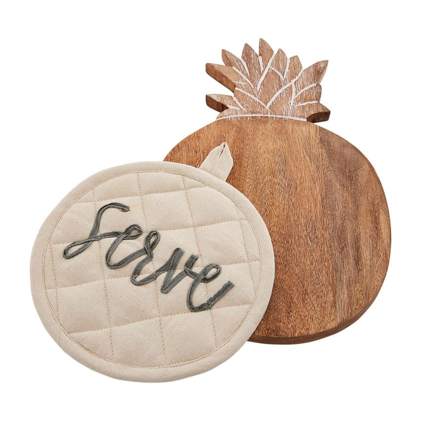 A round wooden trivet with engraved pineapple leaf detail at the top.  The engraving is white.  On top of the trivet is a round quilted off white potholder with embroidery that says 'serve' in cursive lowercase gray font.