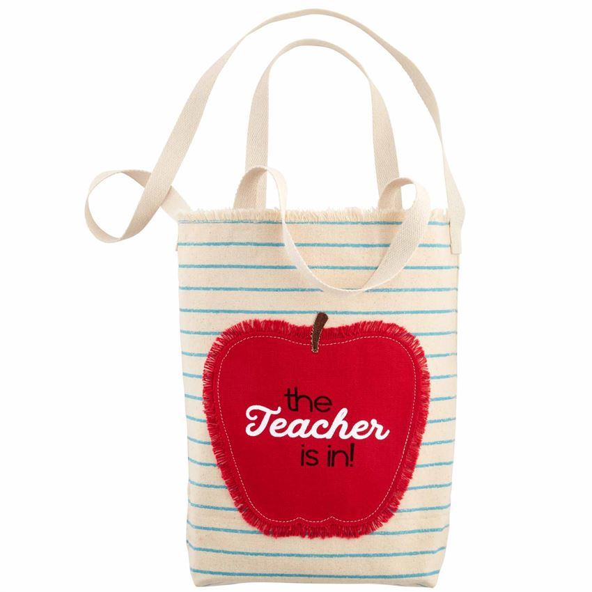 Cotton tote bag with handles.  Face of bag has blue lines to look like a note book page with a gently frayed top.  An apple appliqué with frayed edges is stitched on the side with the text that says ' The Teacher is in!""