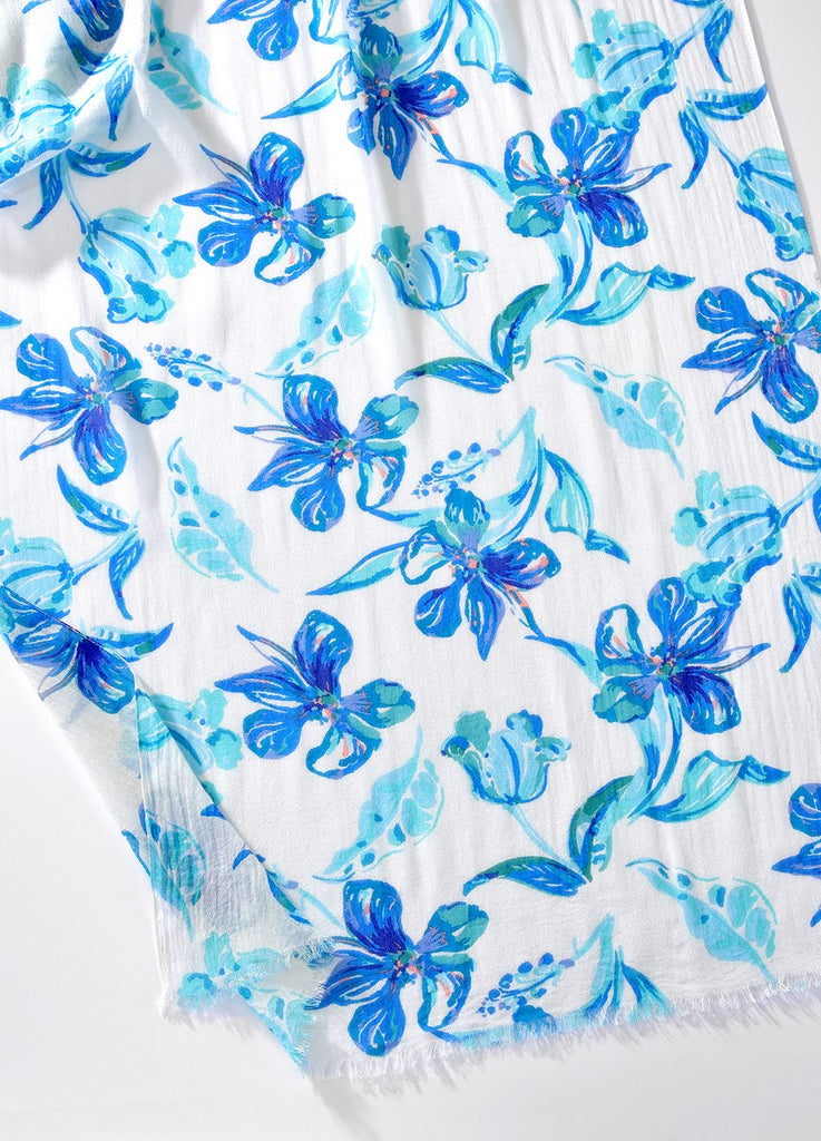 Closeup of Printed white viscose scarf with large blue flowers and lightly frayed edges