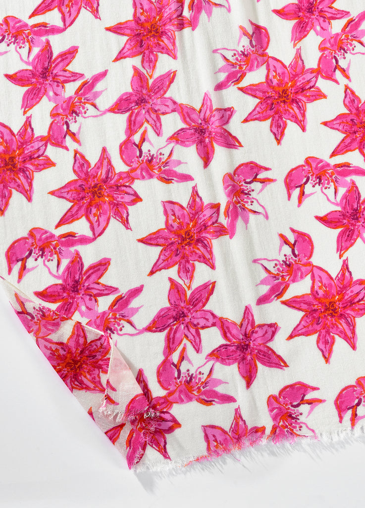 Closeup of Printed white viscose scarf with large pink flowers and lightly frayed edges