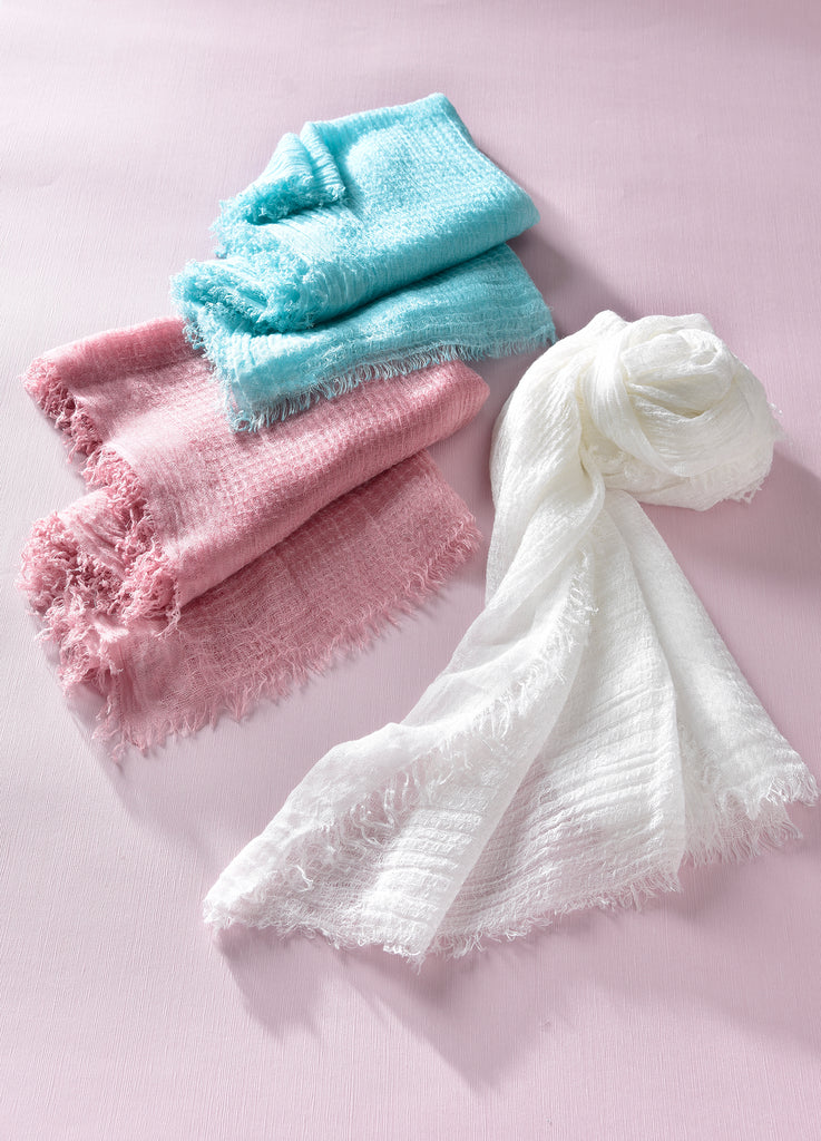 3 waffle textured scarves, one white, one blue, and one pink