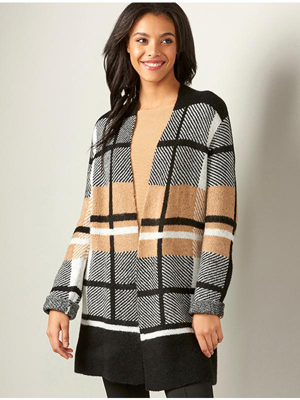 Model wearing an open front plaid cardigan.  The plaid pattern oversized in black, white and camel.  Open front.