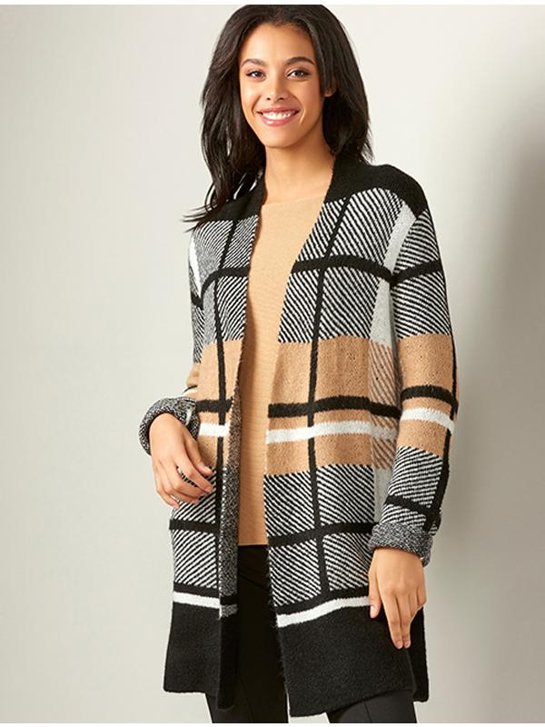 Model wearing an open front plaid cardigan.  The plaid pattern oversized in black, white and camel.