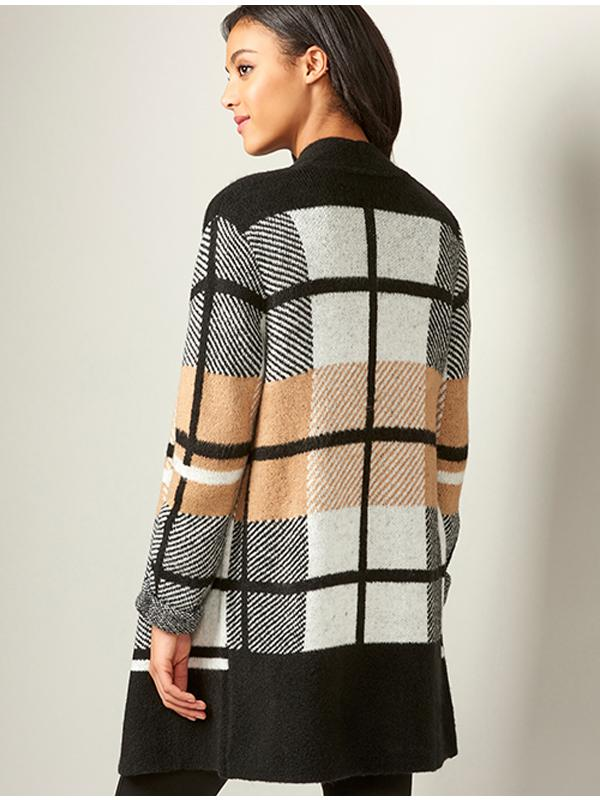Model wearing an open front plaid cardigan.  The plaid pattern oversized in black, white and camel.  View from the back.