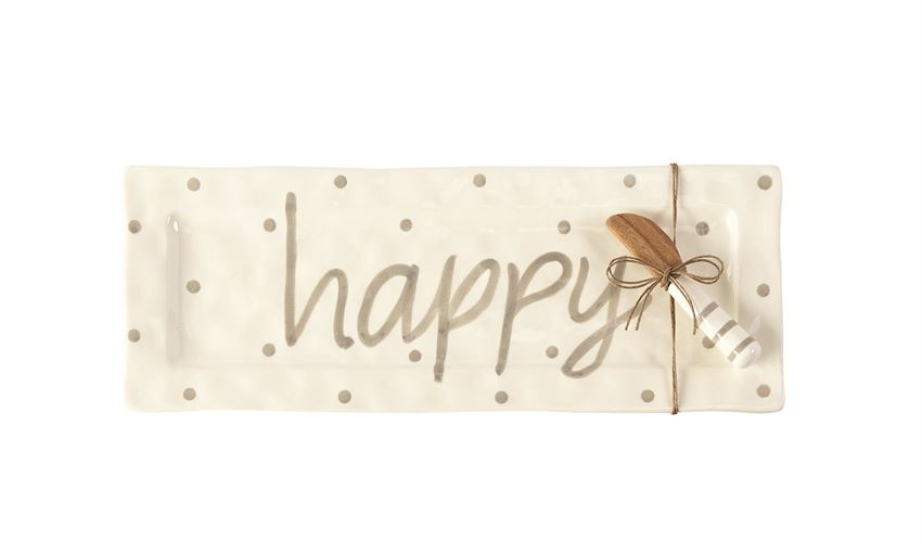 White ceramic platter with gray polka dots and text that says 'happy'.  Coordinating serving knife with wooden plate and striped handle is tied to the platter with twine.