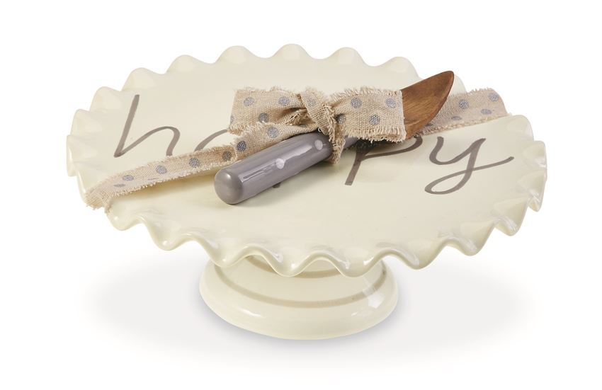 White ceramic cake pedestal that says 'happy' on it in gray text.  A coordinating serving knife with a wooden finish and a gray handle with polka dots is tied to the pedestal with polka dotted ribbon.