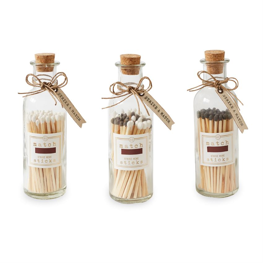 Three different corked glass bottles of 60 long match sticks with canvas printed tag and match striking label.  Left bottle has matches with white heads, the middle bottle a mix of gray and white, and the right bottle all gray