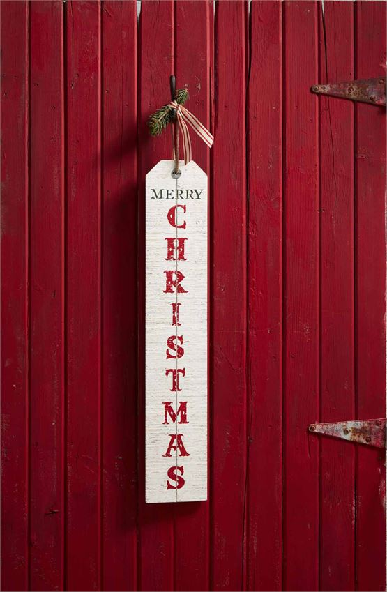 Back of 'Welcome' Sign, wooden distressed white washed sign with jute loop at the top for hanging.  'Merry Christmas' is written horizontally in dark green text above 'Christmas' which is lettered vertically in a red font.  Sign is hung from a nail on a red slatted wooden door.