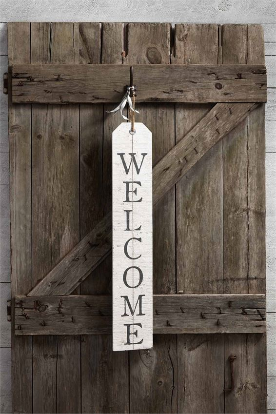 Wooden distressed white washed sign with jute loop at the top for hanging.  'Welcome' is lettered vertically in a gray serif font.  Sign is hung from a hook on a rustic wooden shutter.