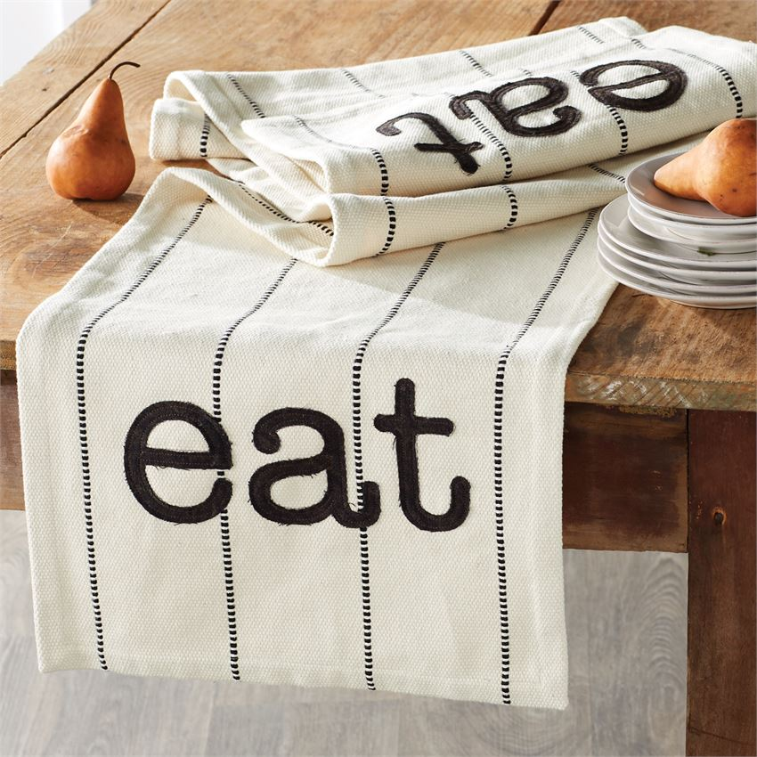 Cotton tan table runner with embroidered lines and appliqué text at each end that says 'eat'.  Runner is folded up at the edge of a wooden table, with one end hanging off.  A stack of plates with a pear on top is on the right, and a single pear is on the left of the runner.