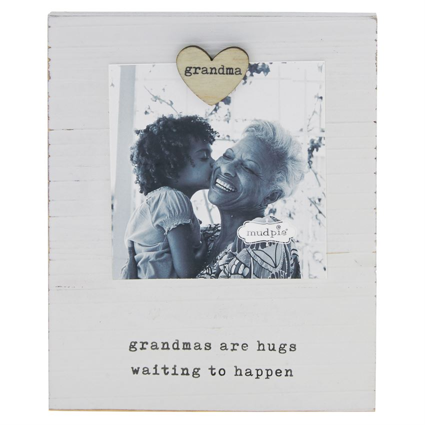 White wooden board with a heart shaped magnet that says 'grandma' on it.  The magnet holds a photo of a granddaughter and her grandmother above a printed saying 'grandmas are hugs waiting to happen'.