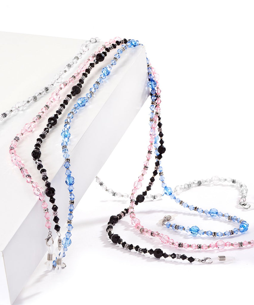 A collection of 4 glass beaded lanyards on a white background draped over a white angled set piece.  From left, there is clear, pink, black, and blue.  Each lanyard cascades off the set piece and collects on a lower level showcasing the lanyards flexibility and facets of the crystals.