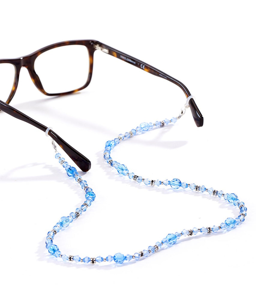 A blue crystal lanyard attached to a pair of tortoise shell glasses.  The angle of the image is from the back of the glasses and the lanyard is in the foreground.