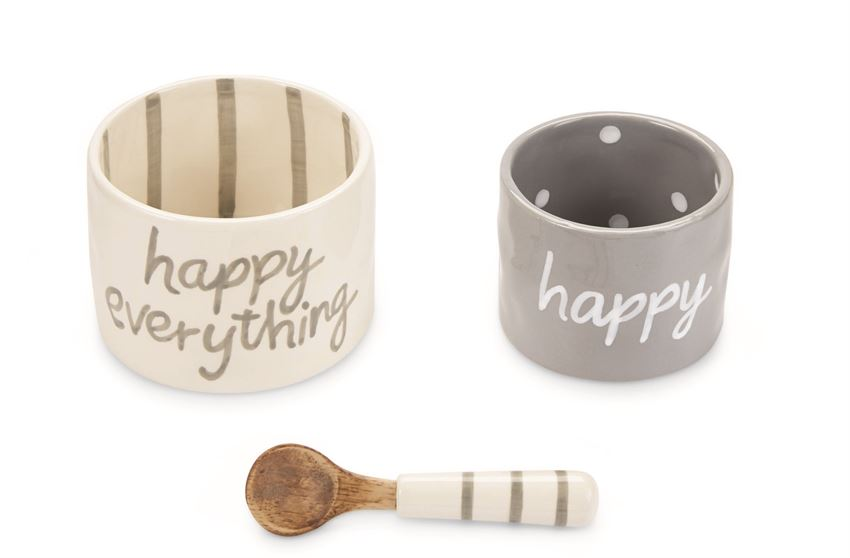 Ceramic bowl set with coordinating spoon.  White bowl says 'happy everything' on the outside, and has matching gray vertical stripes on the inside.  Gray bowl is slightly smaller and says 'happy' on the outside, with matching white polka dots in the inside.