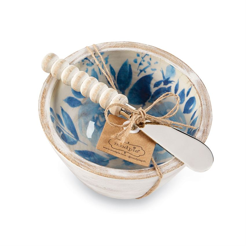 White bowl with blue flower interior and a spreader with a white wood bead handle tied together with twine