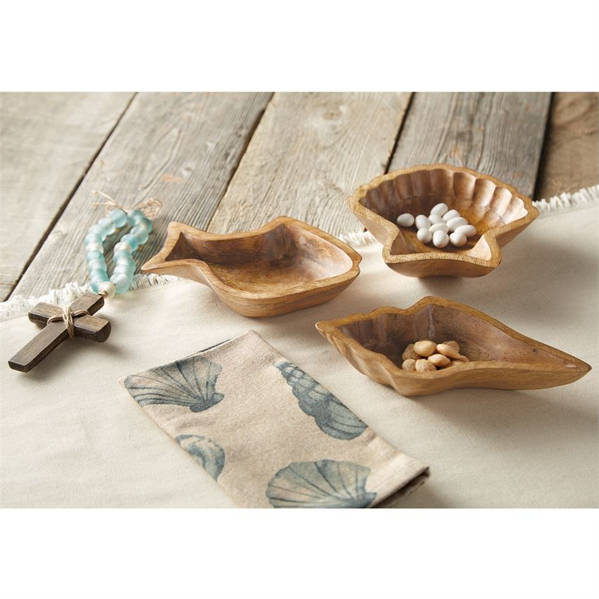 A collection of wooden bowls, one shaped like a fish, a fan shell, and a conch shell, next to a cross with sea glass beads and a napkin with watercolor shells on it.